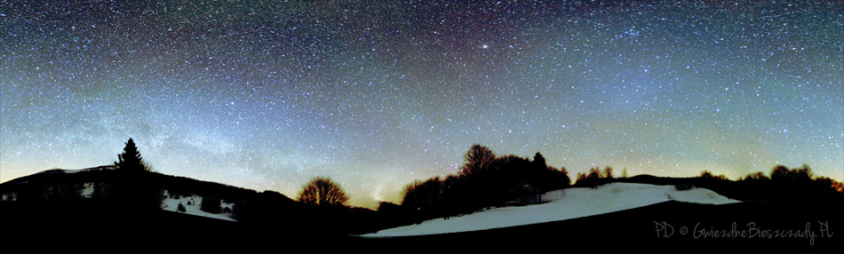 """Na zdjęciu po środku widoczne pasy światła typu """"airglow"""" lub """"niebieską poświatą"""". W środkowej części kadru widoczny jaśniejszy """"obłok"""" to tzw. przeciwblask - część światła zodiakalnego. To międzyplanetarny pył, na którym rozprasza się słoneczne światło. W lewej części kadru widoczna Droga Mleczna. Zdjęcie wykonane parkingu na Przełęczy Wyżniańskiej pod Małą Rawką nad ranem 18 marca.2013. Fot. Pavol Ďuriš / Park Gwiezdnego Nieba """"Bieszczady"""" © 2013"""
